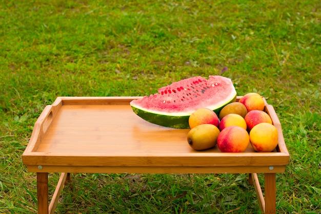 Drewniany stół z owoc na tle zielona trawa.