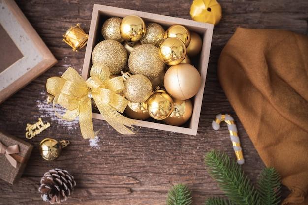 Drewniany stół z ozdób choinkowych ze złotą bombką na pudełku, widok z góry stołu.