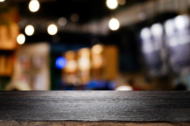 Drewniany stół z plamy tłem sklep z kawą.