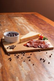 Drewniany stół z przystawką z czarnymi oliwkami, serem, salami i czarnym pieprzem