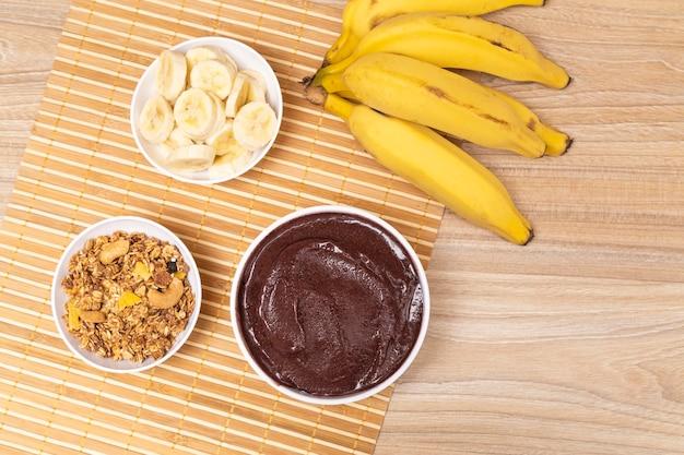 Drewniany stół z pyszną doniczką acai. małe doniczki z granalo i bananem.
