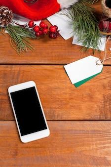 Drewniany stół z telefonem i dekoracjami świątecznymi.