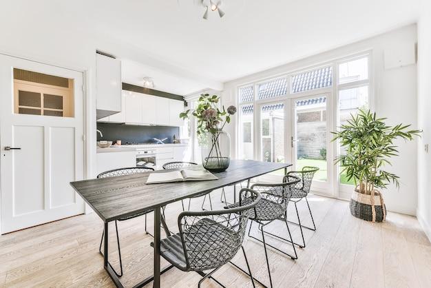 Drewniany stół z wazonem i krzesłami w jasnej jadalni w domu