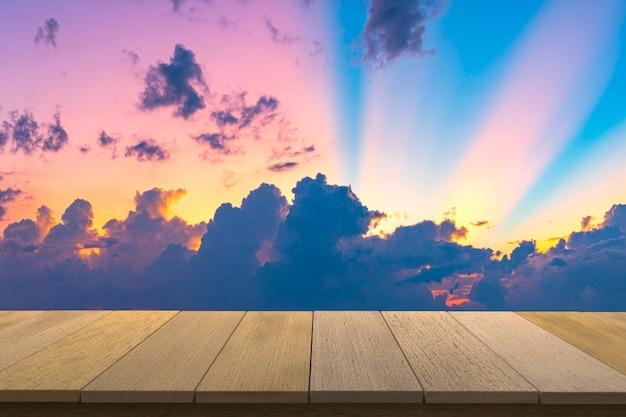 Drewniany stół z widokiem na tle zachodzącego nieba. możesz używać do wyświetlania produktów. copyspace.