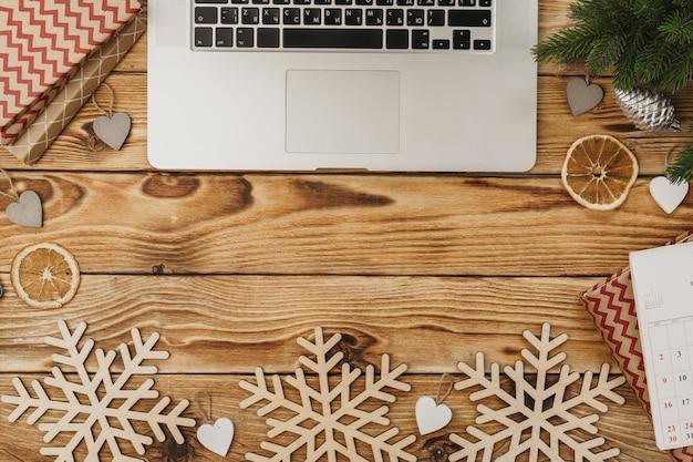 Drewniany stół z wyposażeniem biurowym i papeterią otoczony świątecznym wystrojem nowego roku, widok z góry