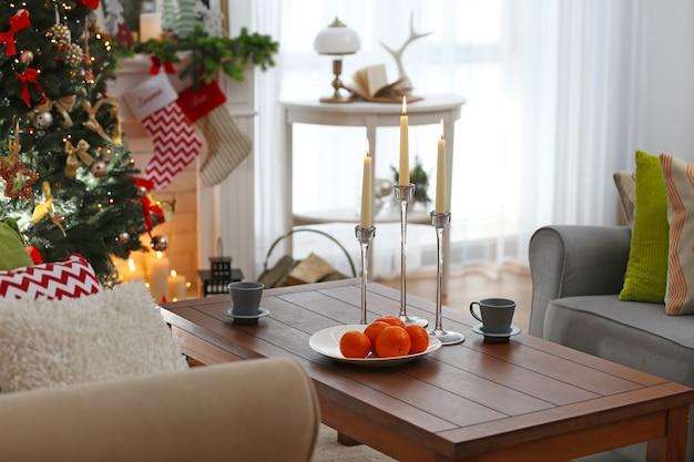 Drewniany stół ze świecami, filiżankami i pomarańczami w salonie udekorowany na boże narodzenie