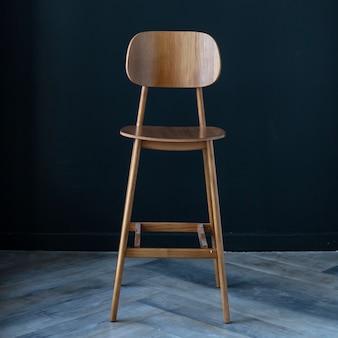Drewniany stołek barowy we wnętrzu na tle ciemnej ściany