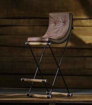 Drewniany stołek ze skórzaną poduszką i metalowymi nogami