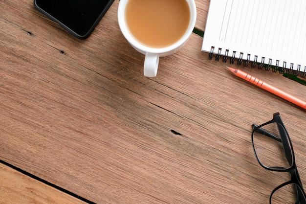 Drewniany stolik z notatnikiem, okularami, długopisem, roślinami ozdobnymi. widok z góry drewniany stół i artykuły papiernicze z miejscem na kopię, leżał płasko.