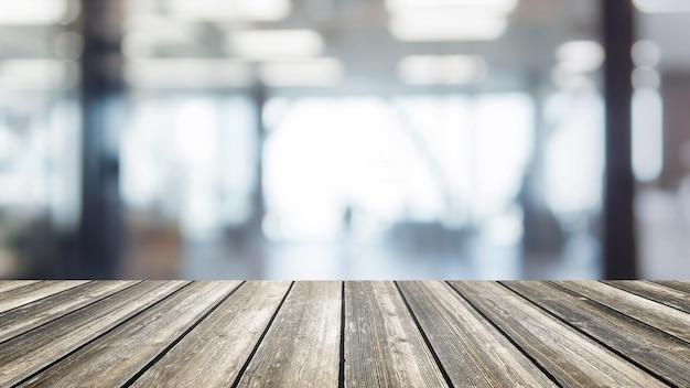 Drewniany stołowy wierzchołek i zamazanego bokeh wnętrza przestrzeni biurowy tło