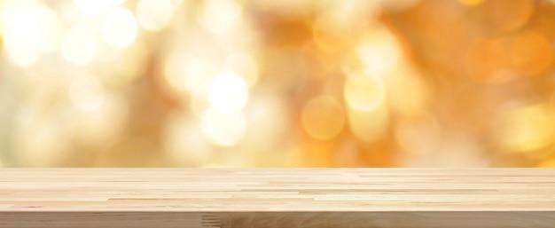 Drewniany stołowy wierzchołek na błyszczącego złocistego bokeh sztandaru abstrakcjonistycznym tle