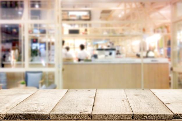 Drewniany stołowy wierzchołek na sklep z kawą tle.