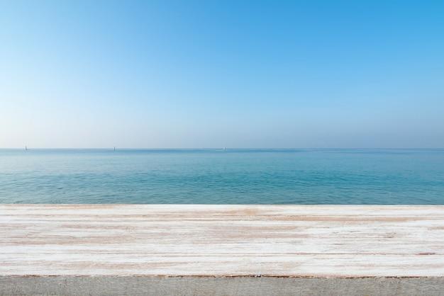Drewniany stołowy wierzchołek na zamazanym błękitnym morzu i białym piasek plaży tle
