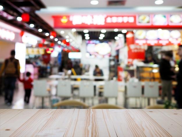 Drewniany stołowy wierzchołek nad chińskiego kluski plamy restauracyjnym tłem.