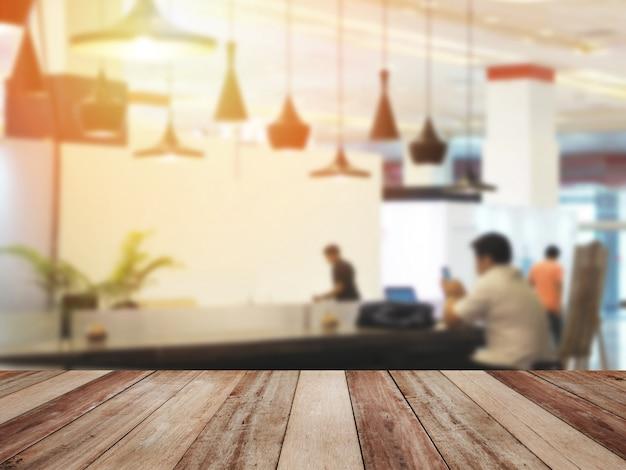 Drewniany stołowy wierzchołek nad ludźmi przy sklep z kawą rozmytym tłem.