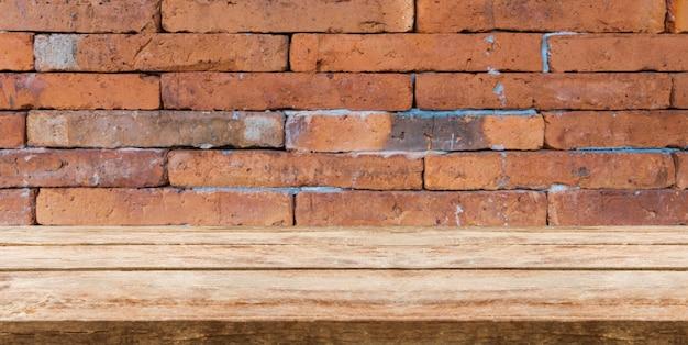 Drewniany stołowy wierzchołek przed ceglaną tła i kopii przestrzenią. wyświetlać lub montować produkty