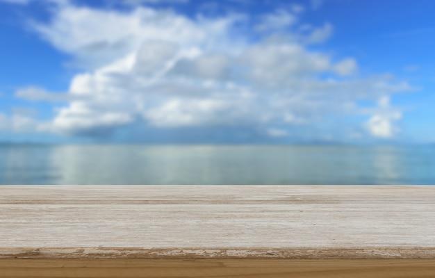 Drewniany stołowy wierzchołek z lato błękita plaży nieba zamazanym tłem