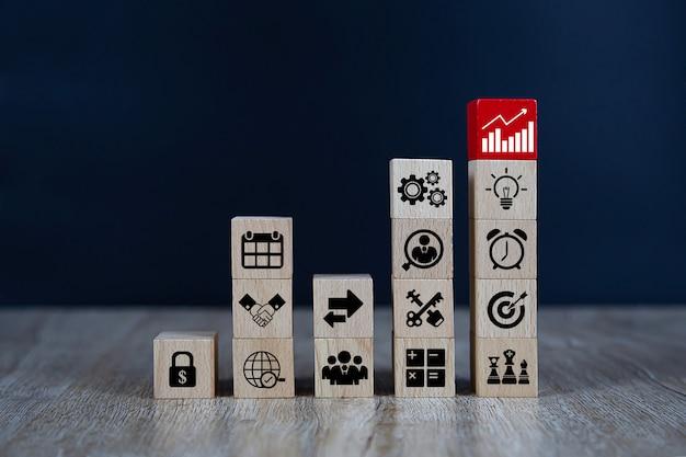 Drewniany sześcian ułożony w kształcie wykresu z ikonami biznesu.