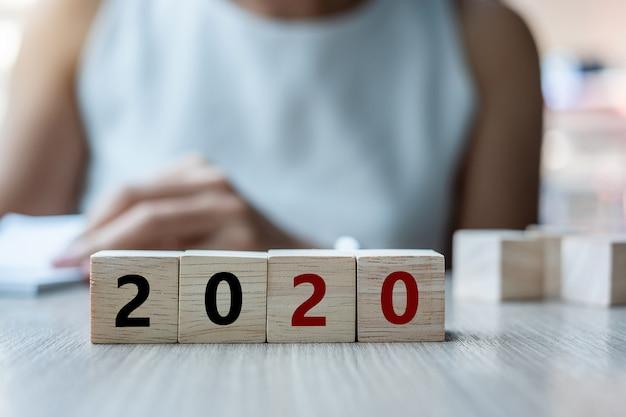 Drewniany sześcian z 2020 słowami na stole