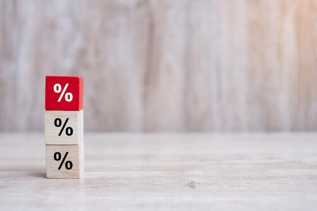 Drewniany sześcian z ikoną symbol procentu. oprocentowanie finansowe