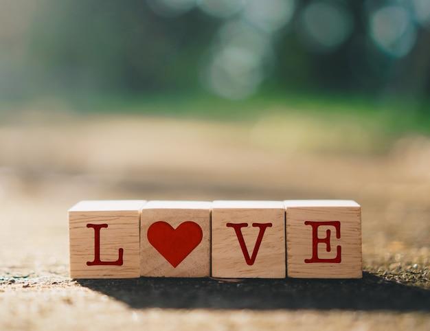 Drewniany sześcian z ikoną znaku serca na i skopiuj światło słoneczne natury przestrzeni możesz umieścić tekst na tle. koncepcja sezon miłości valentine.