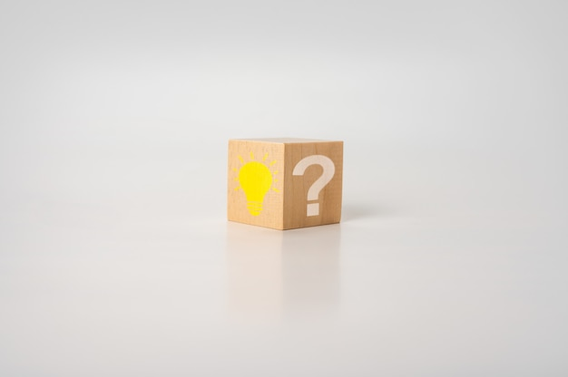 Drewniany sześcian z jasną żarówką i znakiem zapytania na białym stole. kreatywny pomysł, koncepcje innowacji i rozwiązań. drewniany sześcian z ikoną żarówki i symbolem znaku zapytania.