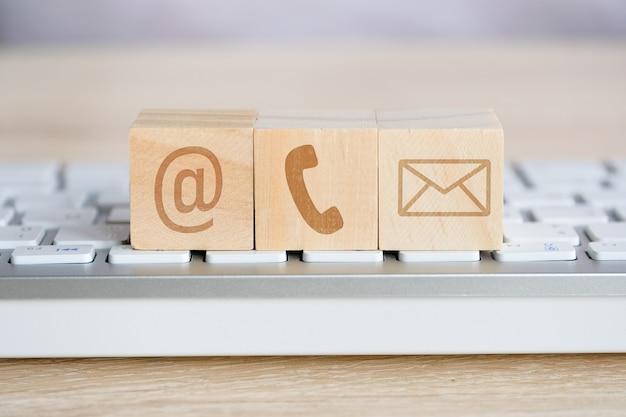 Drewniany sześcian z symbolami obrazkowymi wiadomości e-mail, telefonu i poczty. kontakt w sprawie komunikacji.