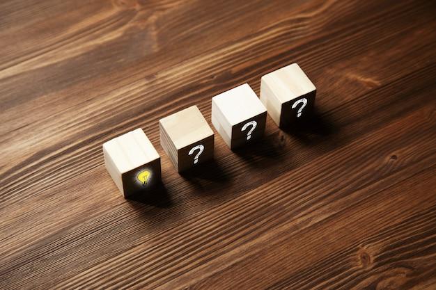 Drewniany sześcian z symbolem znaku zapytania i ikoną żarówki