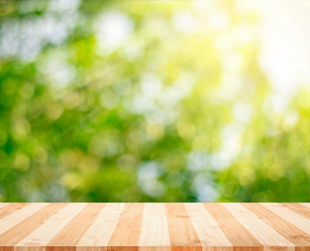 Drewniany tabletop z świeżą zieloną naturą zamazywał tło