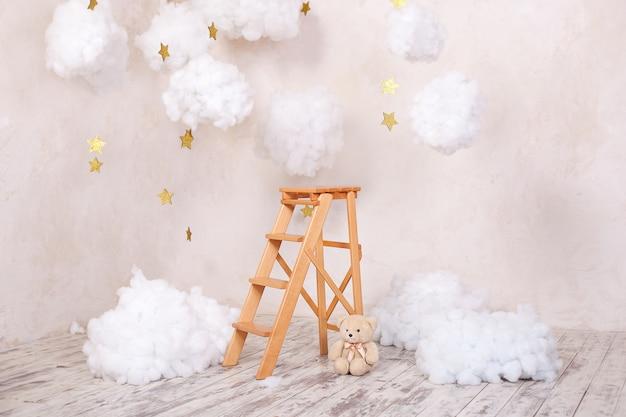 Drewniany taboret schodowy z chmurami w pokoju dziecięcym. styl skandynawski. wnętrze pokoju w stylu rustykalnym. ozdoby choinkowe.
