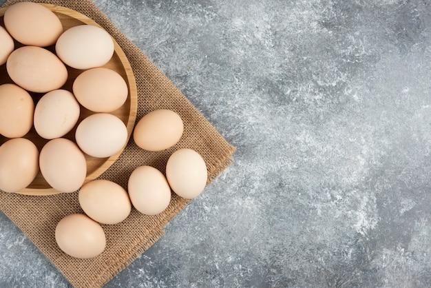 Drewniany talerz ekologicznych niegotowanych jaj na marmurowej powierzchni.