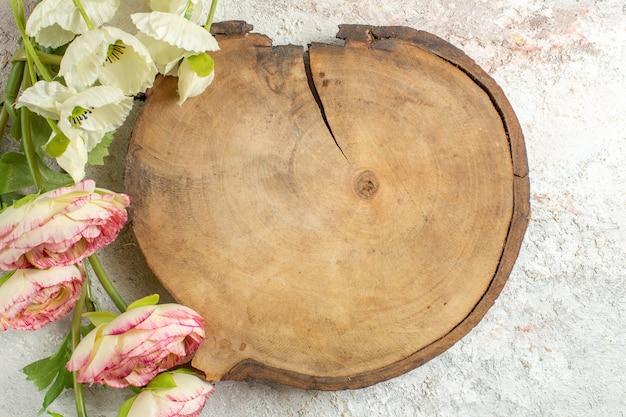 Drewniany talerz i kwiaty na białym marmurowym tle