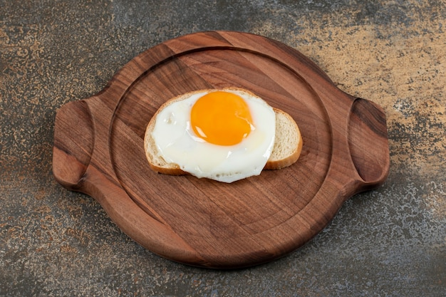 Drewniany talerz jajka na kromce białego chleba.