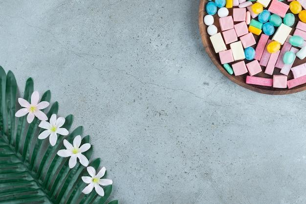 Drewniany talerz kolorowych gum do żucia na kamiennej powierzchni.