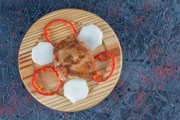 Drewniany talerz kotleta z kurczaka z pokrojoną papryką.