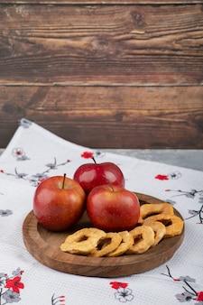 Drewniany talerz krążków suszonych jabłek i czerwone jabłko na białym obrusie.
