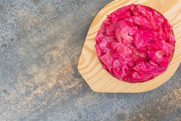 Drewniany talerz pełen czerwonej słonej kapusty na marmurowym tle. zdjęcie wysokiej jakości