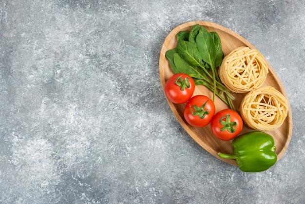 Drewniany talerz pełen surowego makaronu i warzyw na marmurowej powierzchni.