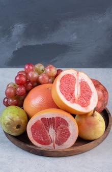 Drewniany talerz pełen świeżych organicznych owoców.