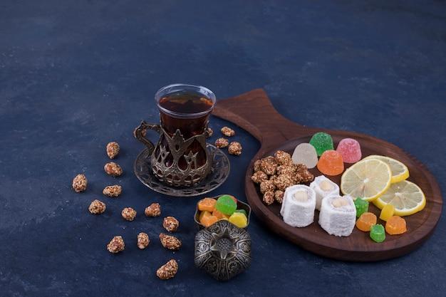 Drewniany talerz przekąsek z marmoladą i szklanką herbaty