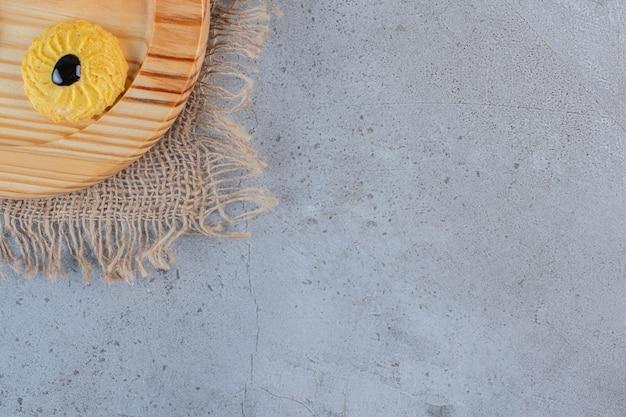 Drewniany talerz pysznego okrągłego ciastka na kamiennym tle.