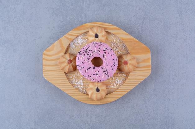 Drewniany talerz pysznego różowego pączka ze słodkim ciasteczkiem.