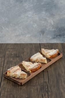 Drewniany talerz pysznych kawałków ciasta z kokosową posypką na drewnianym stole.
