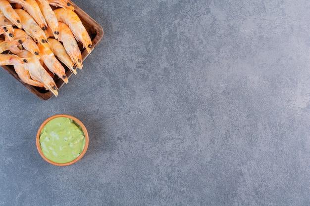 Drewniany talerz pysznych krewetek z sosem na kamiennej powierzchni