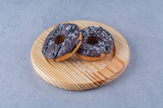 Drewniany talerz pysznych pączków czekoladowych z posypką.