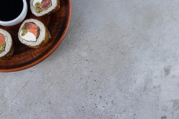 Drewniany talerz rolek sushi z tuńczykiem na kamiennym tle.