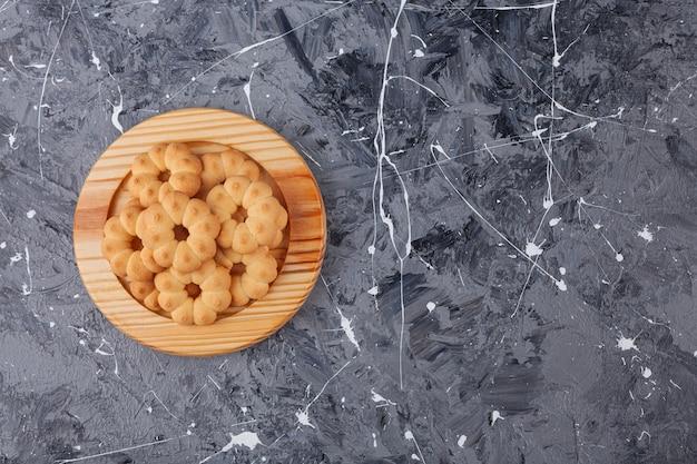 Drewniany talerz słodkich ciasteczek w kształcie kwiatków na tle marmuru.