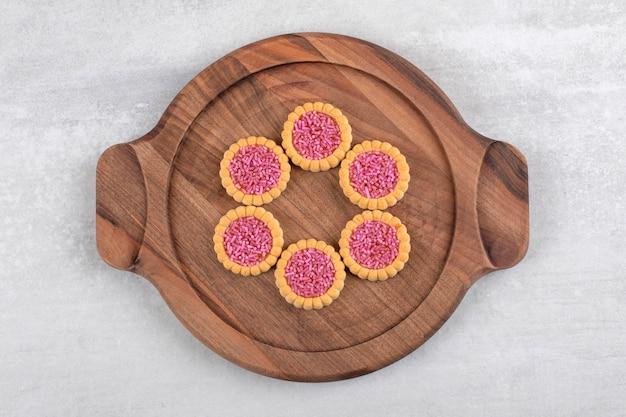Drewniany talerz słodkich ciasteczek z różową posypką na kamiennym stole.