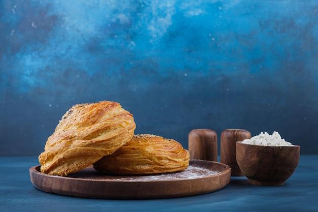 Drewniany talerz słodkich wypieków z nasionami na niebieskiej powierzchni.