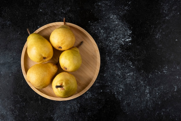 Drewniany talerz smaczne żółte gruszki na czarnej powierzchni.